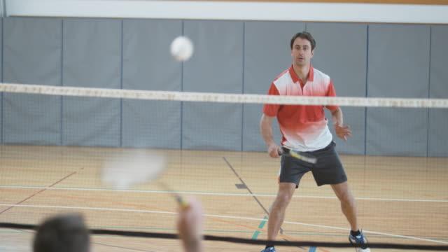 Deux hommes jouant badminton indoor - Vidéo