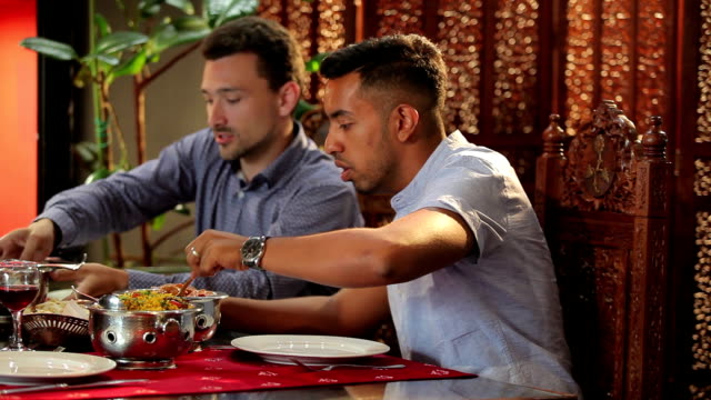 Two men puts the food into the plate in restaurant
