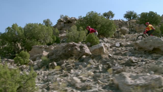 two men ride mountain bikes down rocks in the desert - bike tire tracks video stock e b–roll