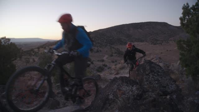 two men ride mountain bikes up a hill in a desert - bike tire tracks video stock e b–roll