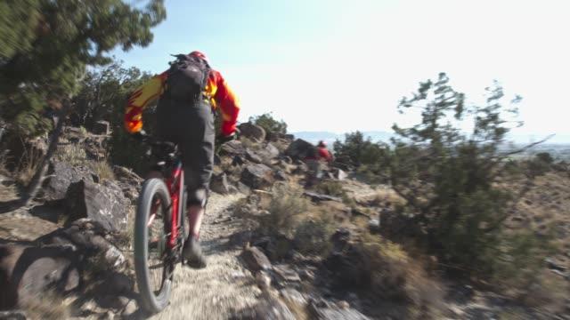 two men ride mountain bikes up rocks in the desert - bike tire tracks video stock e b–roll