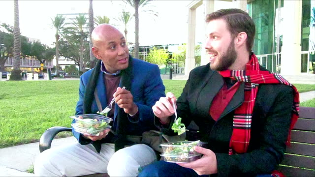 two men sitting on bench eating lunch, talking - debate стоковые видео и кадры b-roll