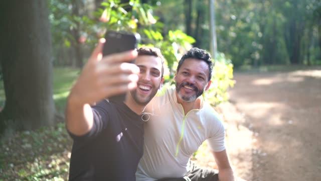 zwei männer, die ein selfie im park machen - gay man stock-videos und b-roll-filmmaterial
