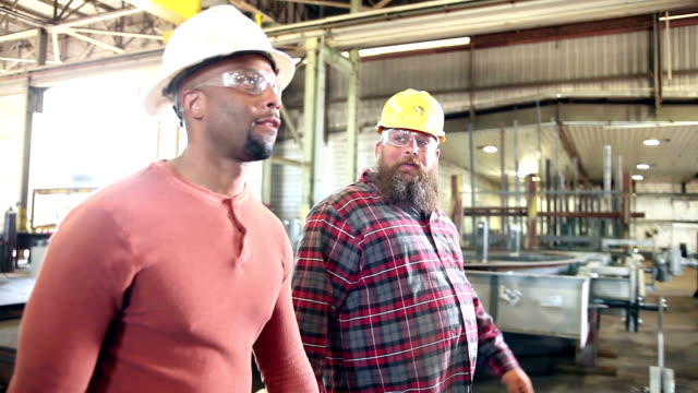 two men talking, walking through metal fabrication shop - occhiali protettivi video stock e b–roll