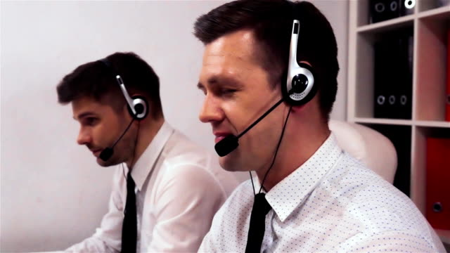 Two men with headsets talking on voice call centre