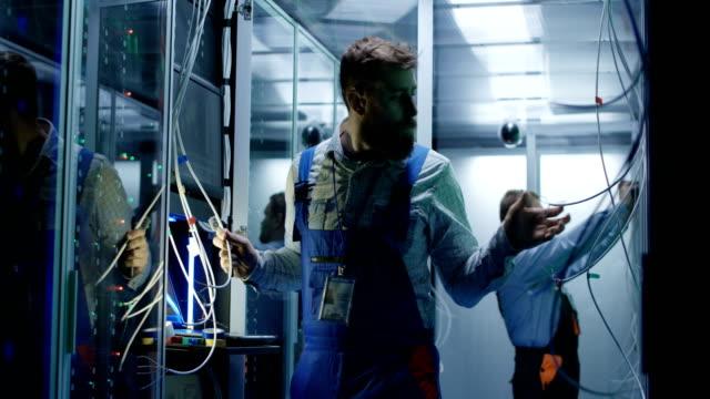 två män som arbetar i ett datacenter - server room bildbanksvideor och videomaterial från bakom kulisserna