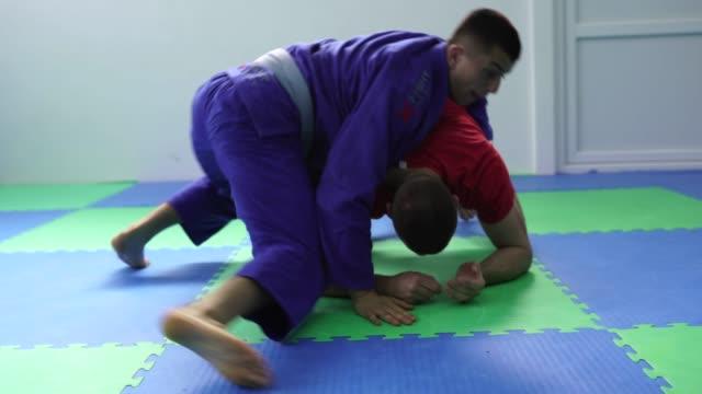 Two men wrestling on the floor in gym