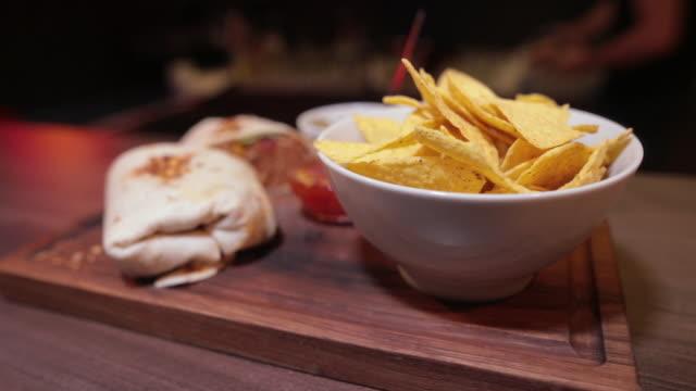 vidéos et rushes de deux burritos mexicains de steak avec des croustilles et la sauce dans le bol sur la planche en bois dans le pub - croustillant