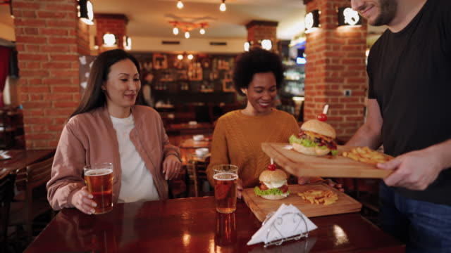 Two mid adult women enjoy beer and burgers in pub video