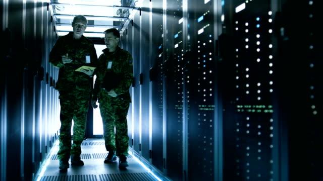 データ センターの廊下で歩いて 2 つの軍人。1 つは、タブレット コンピューターを使用して、ディスカッションです。その両側がデータ サーバーの作業を行 - デイフェンス点の映像素材/bロール