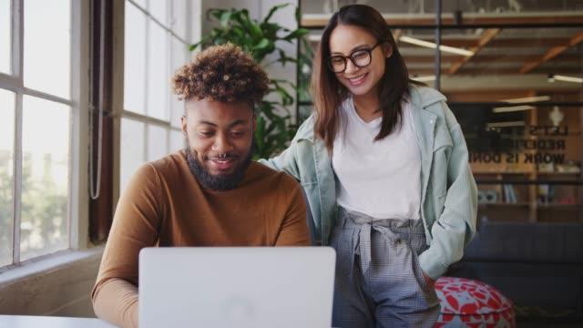 due creativi millennial che guardano un laptop insieme a una scrivania in un ufficio, da vicino - collega video stock e b–roll