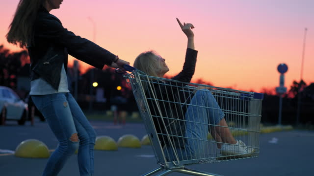Two millennials girlfriends in street clothes have fun in a supermarket parking lot at sunset. Riding a shopping cart, enjoying freedom Two millennials girlfriends in street clothes have fun in a supermarket parking lot at sunset. Riding a shopping cart, enjoying freedom. woman pushing cart stock videos & royalty-free footage