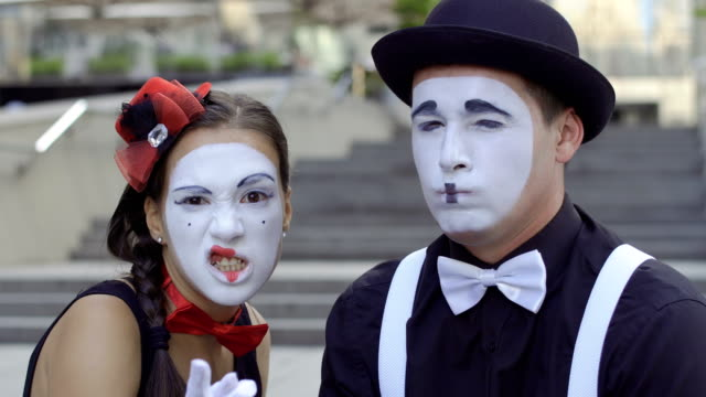 Two mimes suspect something Two funny mimes play a scene. Girl and guy gesticulates their facial expressions. Young amateurs earn money showing people small funny scenes at urban streets. greasepaint stock videos & royalty-free footage