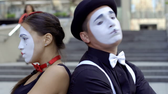 Two mimes take offence at someone's Two funny mimes play a scene. Girl and guy gesticulates their facial expressions. Young amateurs earn money showing people small funny scenes at urban streets. greasepaint stock videos & royalty-free footage