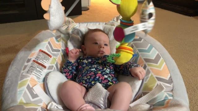 twee maanden oud babymeisje dat met haar speelgoed speelt video