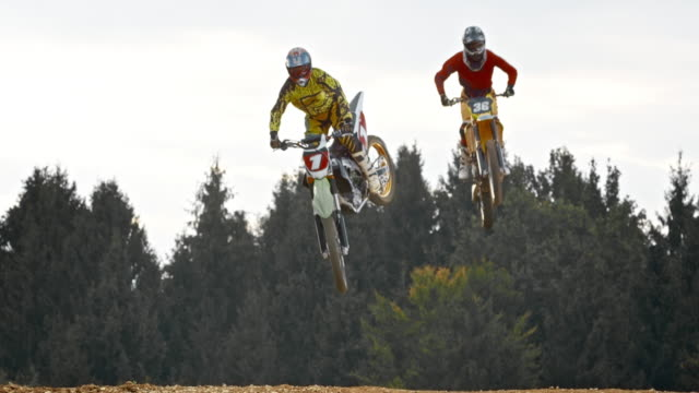SLO MO Two motocross riders jumping into air
