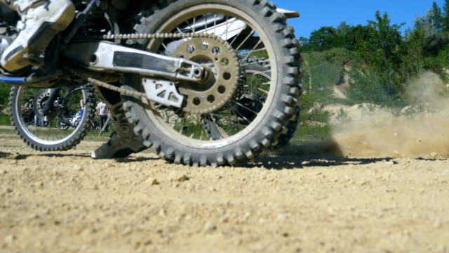 Two motorcycle starting one after another. Studded motocross wheeles starting to spin and kicking up dirt and dust. Slow motion Close up Low angle view Side view