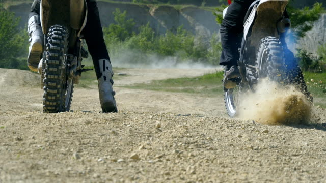 Two motorcycle starting one after another. Studded motocross wheeles starting to spin and kicking up dirt and dust. Slow motion Close up Low angle view Rear back view