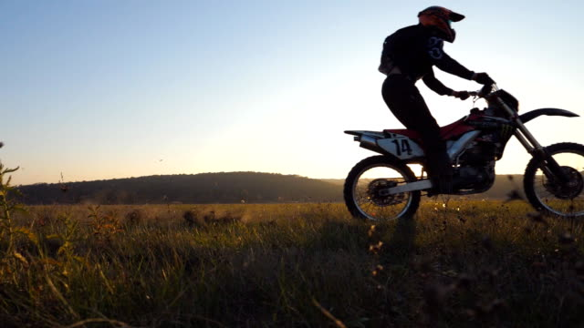 two motorcyclists passing through field with beautiful sunset at background. warm summer sun lights up green vegetation of meadow. friends riders having active rests on nature. extreme sport concept - freestyle motocross video stock e b–roll