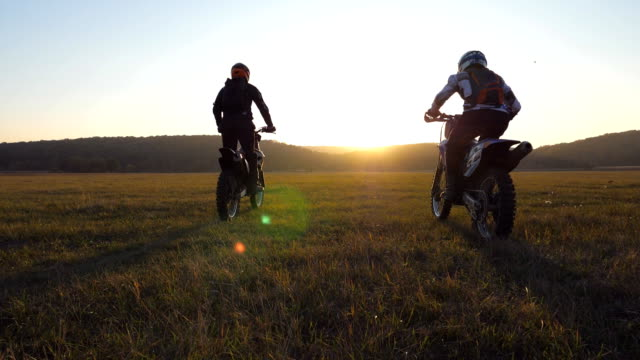 two motorcyclists passing through large field with beautiful landscape at background. bikers rides into sunset. two friends  riders having active rest on nature. extreme sport concept. slow motion - motocross video stock e b–roll