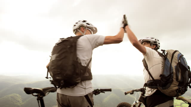SLO MO of two mountain bikers doing the high five video