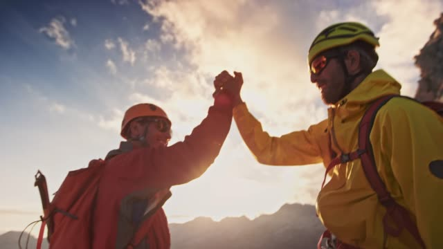 Two mountaineers doing a handshake on mountain top at sunset