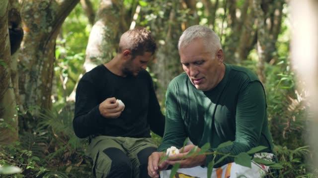 två mountainers som äter kokta ägg i djungeln. - kokat ägg bildbanksvideor och videomaterial från bakom kulisserna