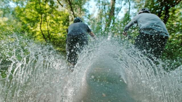 vidéos et rushes de super slo mo deux motards vtt éclaboussant à travers un ruisseau - randonnée équestre