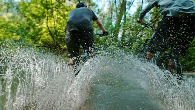 vidéos et rushes de super slo mo time warp effect deux motards vtt éclaboussures à travers un ruisseau - randonnée équestre