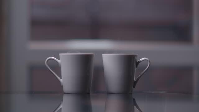 due tazze in una stanza con vapore, tazze stanno aspettando i loro proprietari per una buona serata accogliente insieme - due oggetti video stock e b–roll