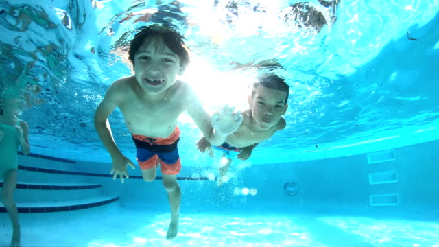 Two multi-ethnic boys swimming underwater in pool Two multi-ethnic boys swimming underwater in a swimming pool. The boy on the left is 8 years old. His friend is 7 years old, mixed race African-American and Caucasian. only boys stock videos & royalty-free footage