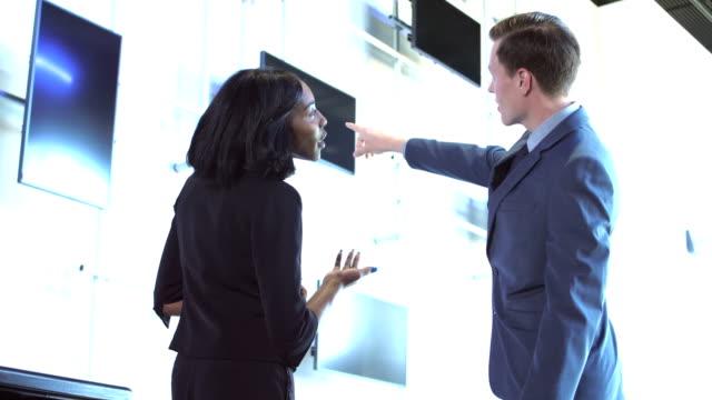 2 つの多民族のビジネス人、指摘して会話 - 展示会点の映像素材/bロール