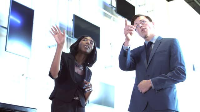 2 つの多民族のビジネス人、指摘して会話 - 指差す 女性点の映像素材/bロール