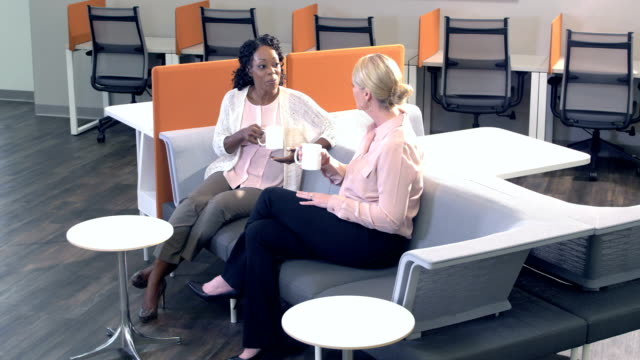 Two multi-ethnic businesswomen taking coffee break Two mature multi-ethnic businesswomen sitting on a couch in an office, friends taking a coffee break, conversing. face to face stock videos & royalty-free footage