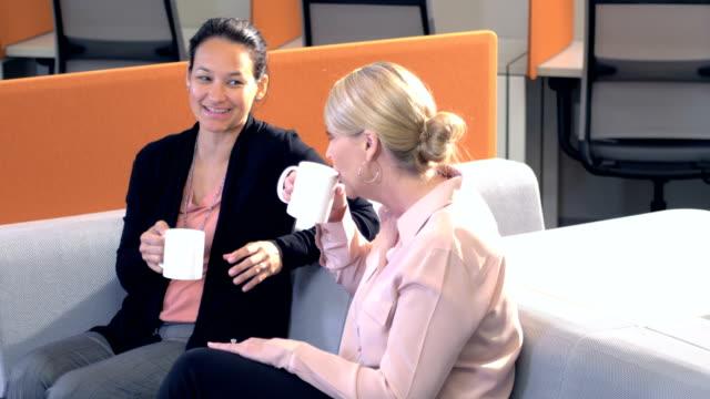 Two multi-ethnic businesswomen taking coffee break