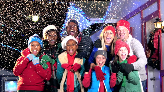 Two multi-ethnic families at winter festival, shouting Two multi-ethnic families having fun at a winter festival. The eight parents and children are standing together outdoors, shouting and laughing, waving at the camera. It is snowing at night, with string lights hanging from the roofs behind them. medium group of people stock videos & royalty-free footage