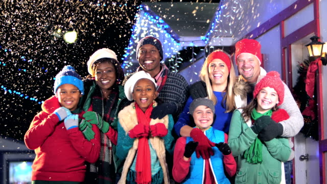 Two multi-ethnic families at winter festival Two multi-ethnic families having fun at a winter festival. The eight parents and children are standing together outdoors, smiling and laughing, looking at the camera. It is snowing at night, with string lights hanging from the roofs behind them. medium group of people stock videos & royalty-free footage