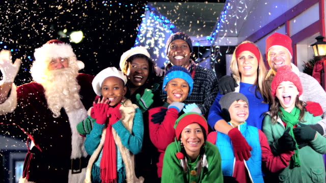 Two multi-ethnic families at winter festival with Santa Two multi-ethnic families having fun at a winter festival, posing with Santa Claus. The eight parents and children are standing together outdoors, smiling and waving at the camera. It is snowing at night, with string lights hanging from the roofs behind them. medium group of people stock videos & royalty-free footage