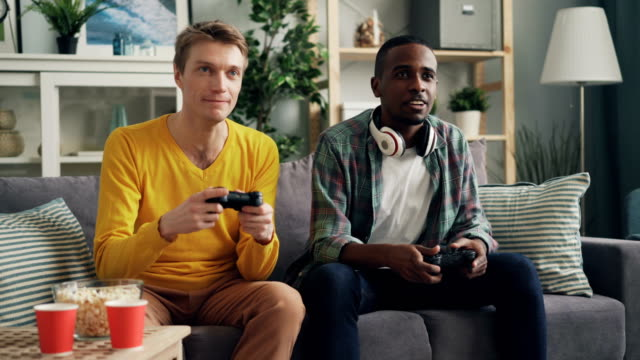 vídeos de stock e filmes b-roll de two multi-ethnic friends playing video game sitting on couch at home - man joystick