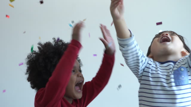 Two multi-Ethnic little boys playing glitter ribbon togerther - vídeo