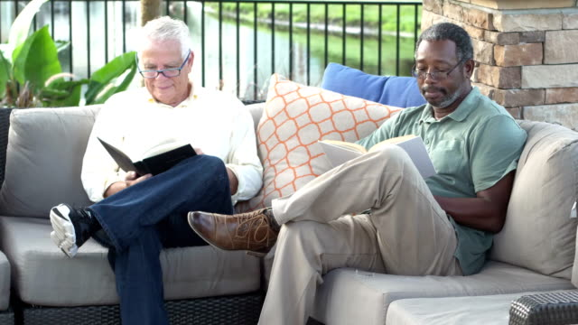 Two multi-ethnic men on patio reading books Two multi-ethnic men sitting on a sofa on a patio reading books. The African-American man is in his 50s and his friend is in his 70s. cross legged stock videos & royalty-free footage