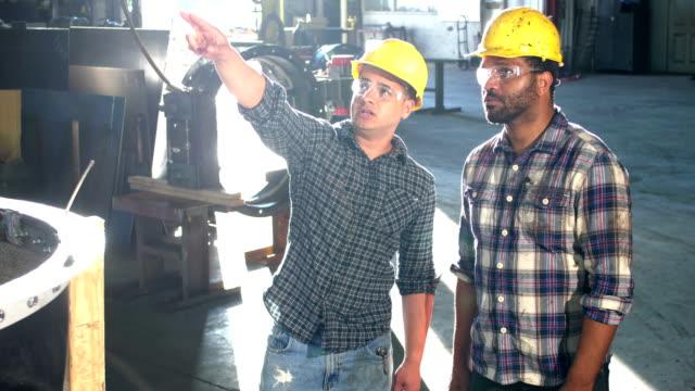 due lavoratori multietnici in un negozio di fabbricazione di metalli - abbigliamento casual video stock e b–roll
