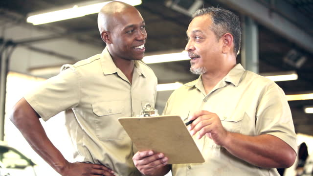 two multi-ethnic workers in warehouse, with checklist - manager stock videos and b-roll footage