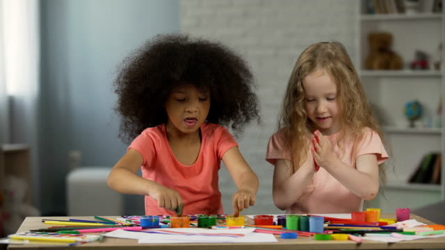 Two multiracial kids sitting at the table and smudging hands with paints video