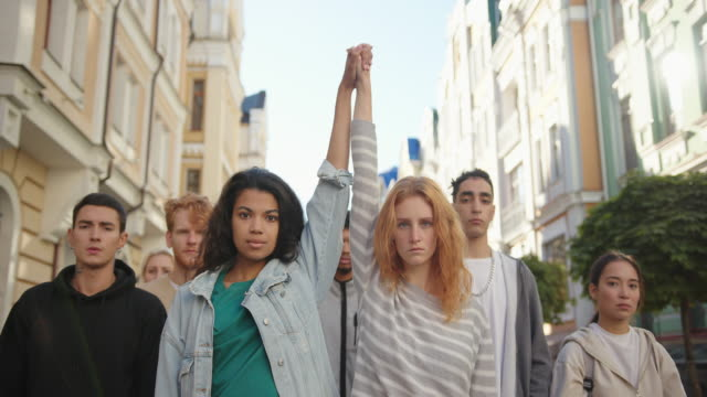 Two multiracial women holding hands together and lift them up in mass protest against racism Two multiracial women holding hands together and lift them up in mass protest against racism. tranquility stock videos & royalty-free footage