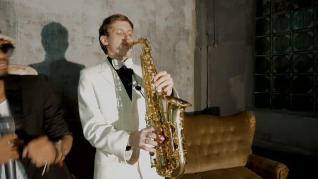 Two musicians show the performance. An African man is singing, a white man is playing the saxophone.