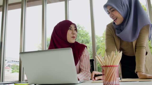 två muslimska affärskvinna i traditionella hijabkläder som arbetar och diskuterar på moderna kontor. nytt normalt koncept. - hijab bildbanksvideor och videomaterial från bakom kulisserna