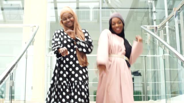 vídeos de stock, filmes e b-roll de duas mulheres de negócios muçulmanas alegres dançando de alegria no trabalho - amizade feminina