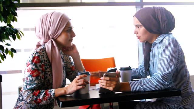 två muslimska kvinnor dricker kaffe och kommunicera - anständig klädsel bildbanksvideor och videomaterial från bakom kulisserna