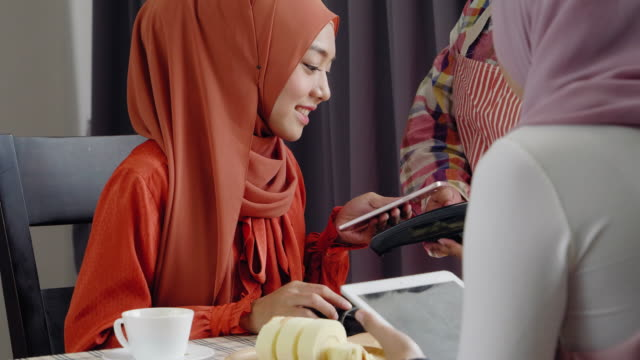 two muslim women eatting food and drink in restaurant use scan and payment on mobile phon,Lifestyle technology concept two muslim women eatting food and drink in restaurant use scan and payment on mobile phon,Lifestyle technology concept souvenir stock videos & royalty-free footage